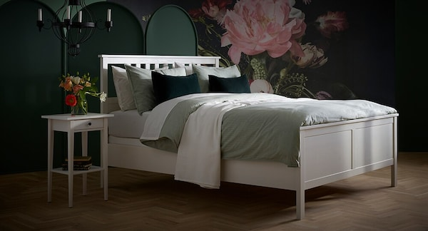 HEMNES queen bed frame in white with green duvet covers and a HEMNES nightstand beside it.