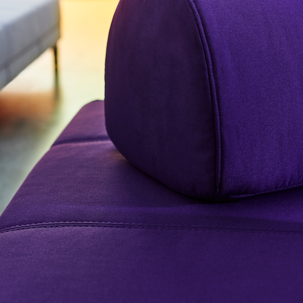 A close-up of the purple FLOTTEBO sofa bed with stitching details and large movable cushions to place as you wish.