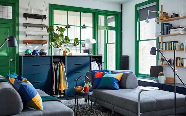 A room with a dark gray sofa bed, blue dresser storage units, and green framed windows and doorways.