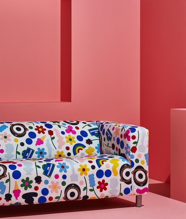 KLIPPAN sofa with a colorful and patterned FÖRNYAD cover, designed by Darcel Disappoints, shown in a pink room.