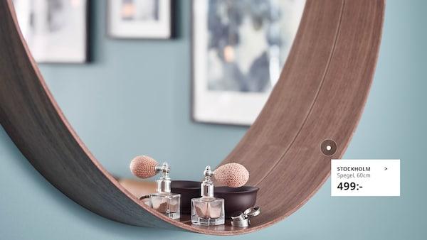 Rund spegel i valnöt på turkos vägg
