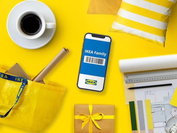 IKEA Family barcode on a mobile phone resting on a yellow background.