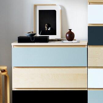 Två MALM byråer sidan om varande med lådfronter som fått ett nytt utseende med dekorplas i olika färger.