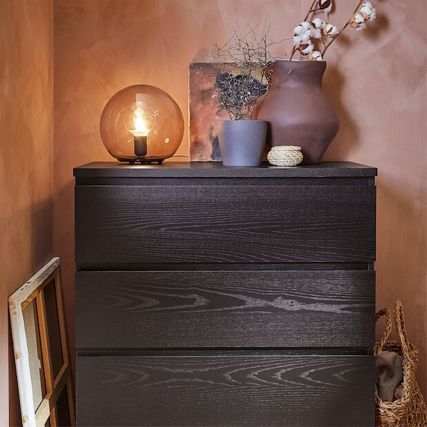 A chest of drawers in black-brown, a terracotta vase, a dark grey plant pot and a grey table lamp.