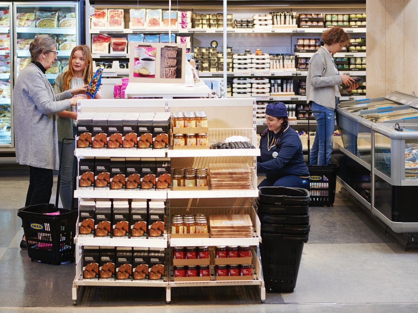 Regály se švédskými specialitami, vedle kterých stojí dvě zákaznice a zaměstnankyně IKEA.