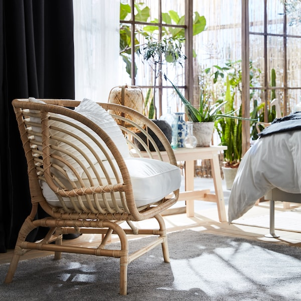 BUSKBO stolica od ratana s bijelim ukrasnim jastucima, tamnosivim i bijelim zavjesama, klupom, zelenim biljkama i sivim tepihom.