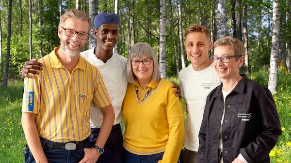 Personal från IKEA som står framför björkar och grönska.