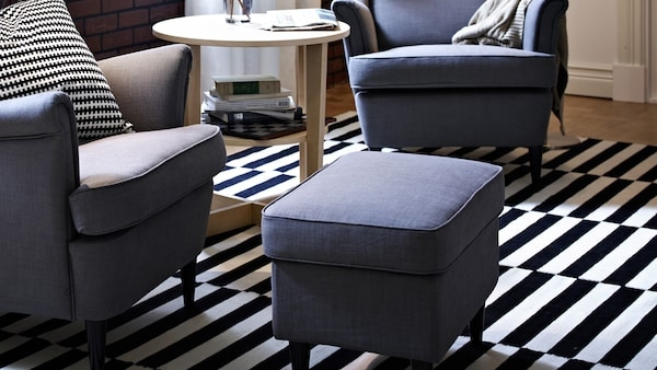 grey chair and footstools on a black and white striped rug