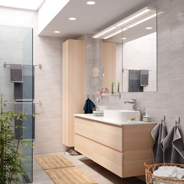 Fürdőszoba, világos tónusokkal, nagy tükörrel és HORVIK mosdóállvánnyal.