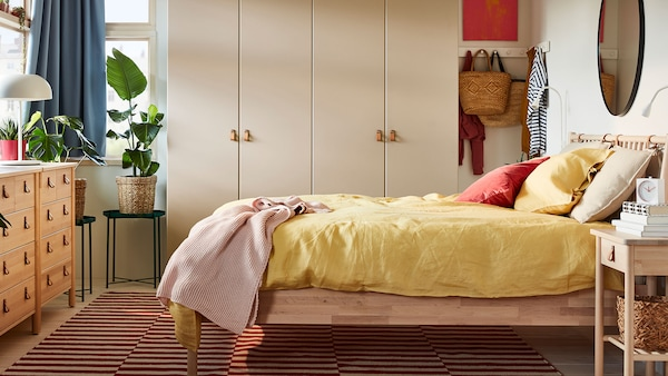Tidy bedroom with BJÖRKSNÄS bed frame and yellow bedding linking to the bedrooms page.