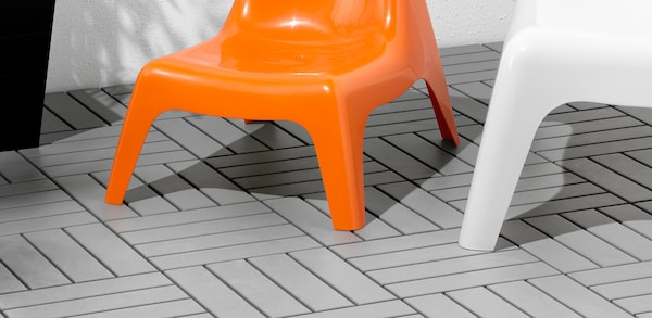 Orange chair sitting on grey outdoor flooring.