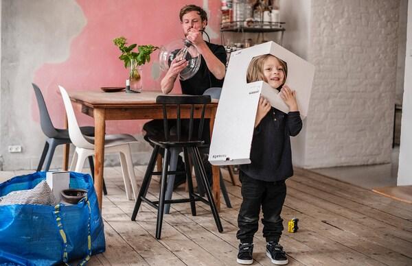 Papà che monta il lampadario mentre il bimbo gioca a fare il supereroe - IKEA