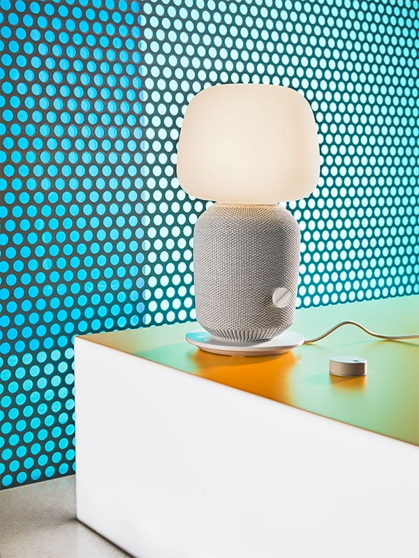 Une lampe SYMFONISK dans une pièce éclairée repose sur une table orange, devant un mur à pois bleus.