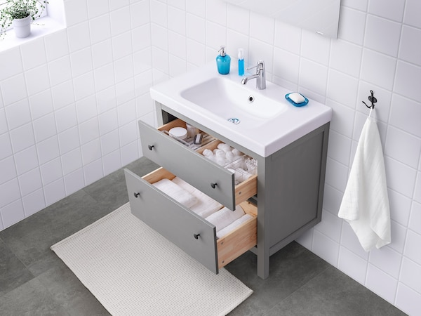 A white bathroom with a gray sink cabinet with the drawers open, displaying bathroom supplies