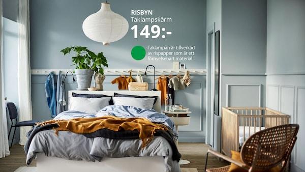 Sovrum med MALM sängstomme med matta under och fåtölj och spjälsäng bredvid