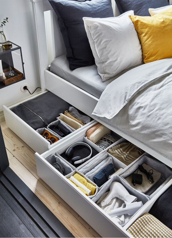 Dvije kutije za odlaganje koje stoje ispod kreveta izvučene su tako da su vidljivi organizirani dodaci u sivim IKEA RAGGISAR košarama.