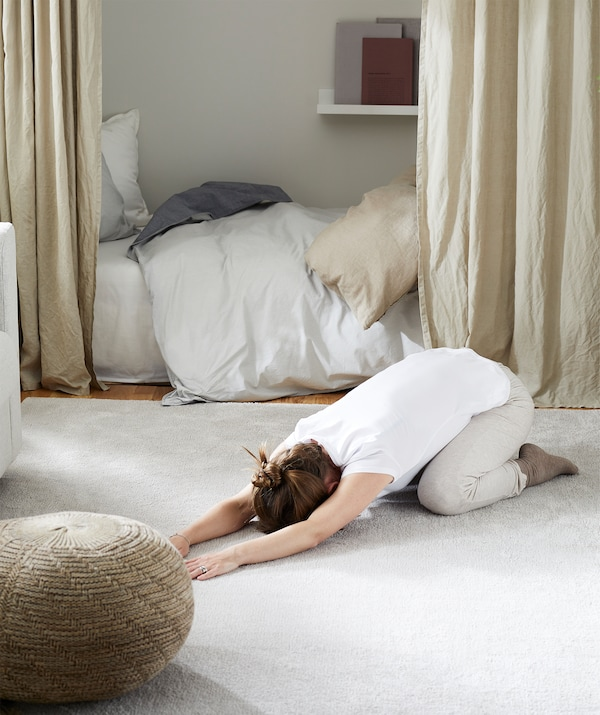Woman lying prostrate, folded legs in an exercise-style position on living-room rug, furniture moved to the side around her.