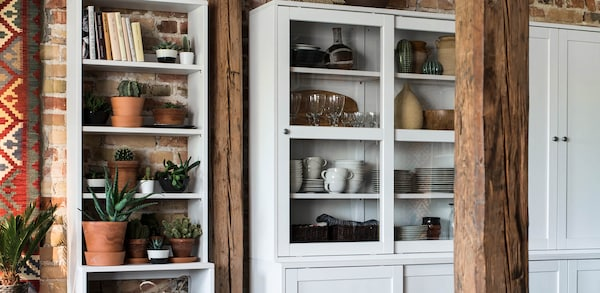 White storage cabinet with sliding solid doors and sliding glass doors, filled with dishes.