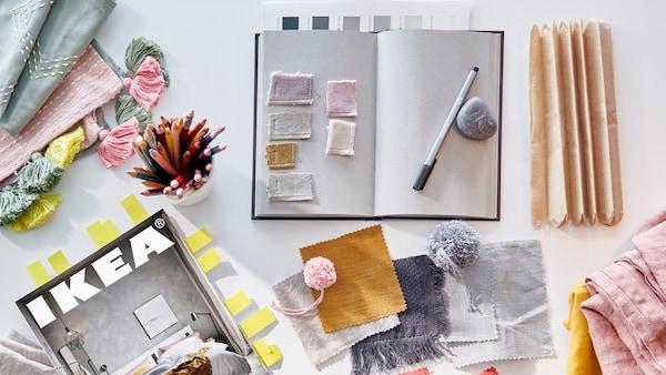 Et skrivebord set fra oven, hvor fyldt med farveprøver, stofprøver, en notesbog og et IKEA katalog.