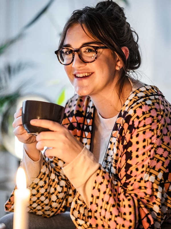 Eine Frau mit Brille trägt einen farbenfrohen Kaftan und hält eine schwarze Tasse in der Hand. Sie sitzt auf einem Sofa.