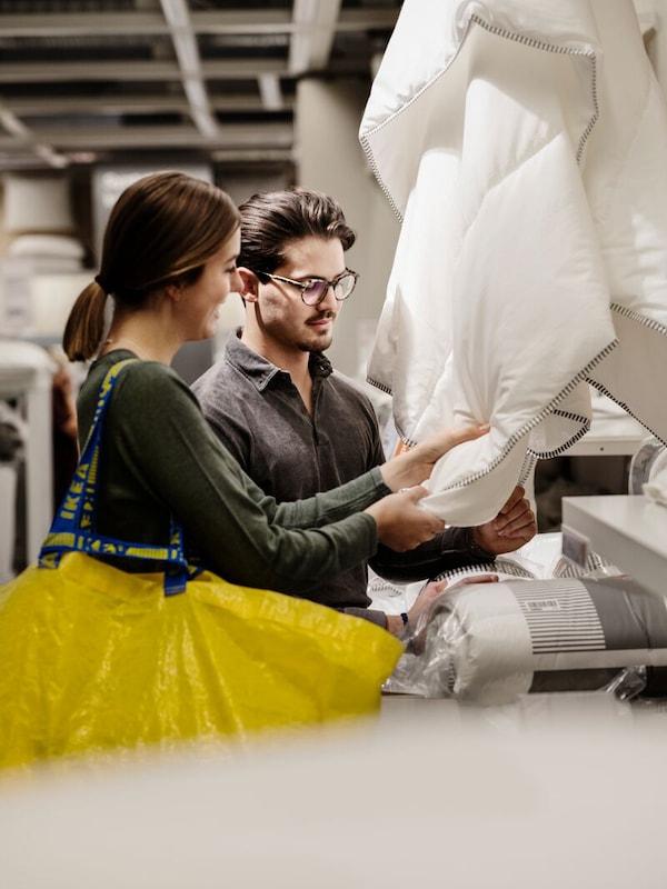 Nuori pariskunta tutustuu IKEA-tavaratalossa ostoksilla peiton tuntuun.
