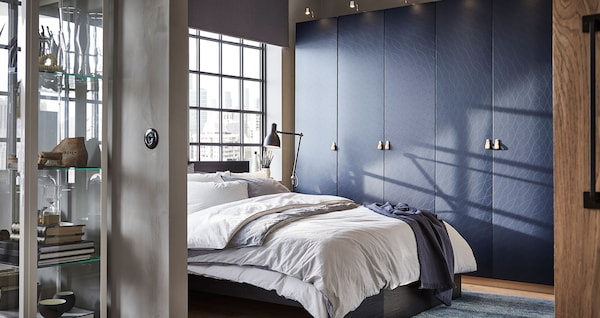A cozy, modern bedroom in blue and brown with a MALM bed