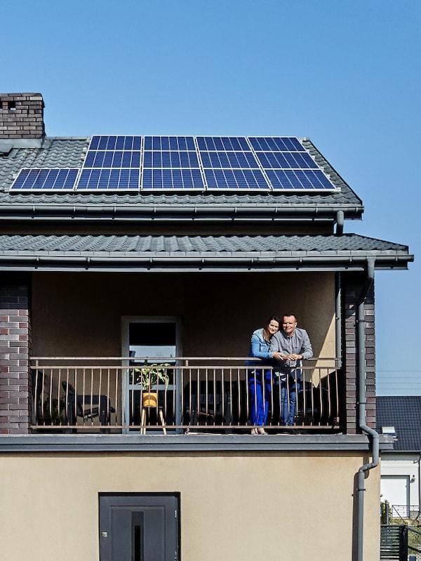Para stojąca na balkonie domu jednorodzinnego z panelami fotowoltaicznymi.