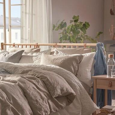 Ett ljust sovrum i skandinavisk stil med gröna växter och en säng bäddad med linnepåslakanset i ljusa färger, på sängbordet står en vattenkaraff med glas.