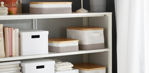 Various neutral colored boxes and organizers on white bookcase