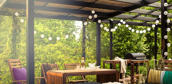 Outdoor covered patio with wooden table and chair set with outdoor decorative string lights hanging around perimeter.