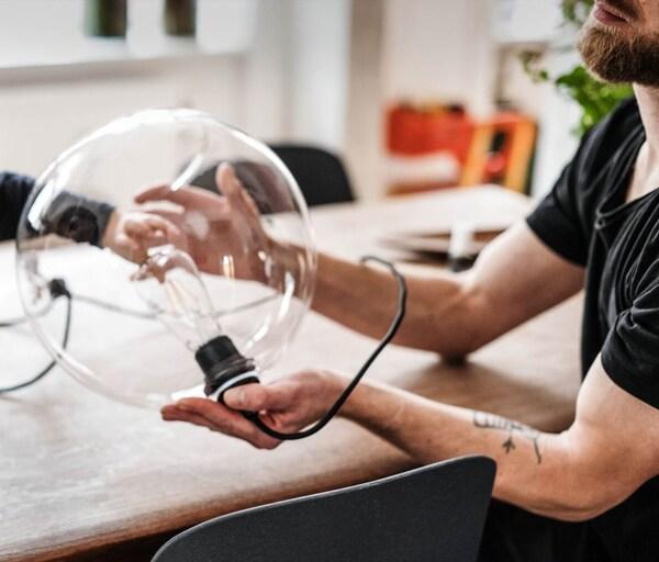 Een man aan tafel terwijl hij een glazen tafellamp vasthoudt.