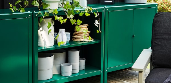 Green Outdoor shelving containing plant holders and gardening tools and outdoor shelves.