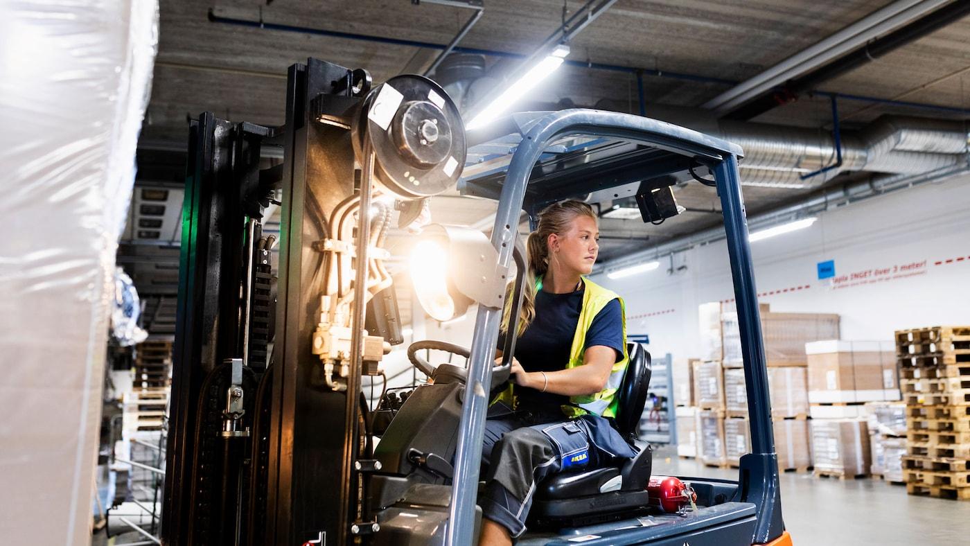En ung kvinna kör en truck inne i en lagerlokal.