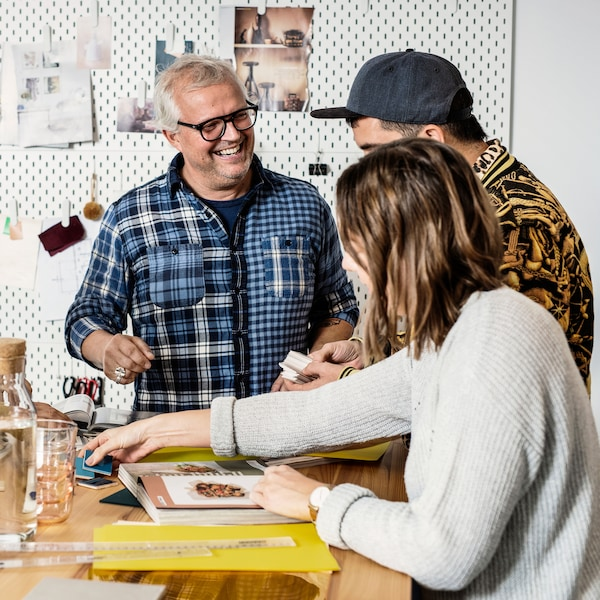 Three IKEA Family members engaging and being creative at a store workshop event.