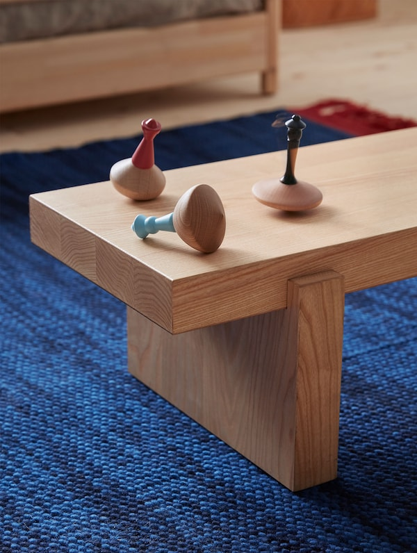 Three VÄRMER spinning tops are on top of a minimal wooden bench and a blue and red woven rug.
