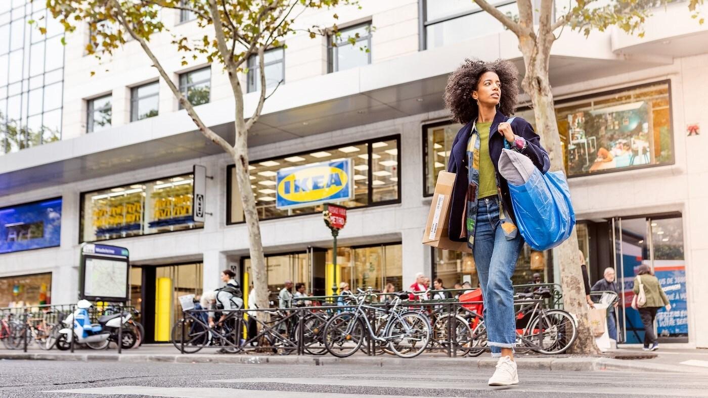 En kvinna med en FRAKTA kasse korsar en gata med en IKEA butik i bakgrunden.