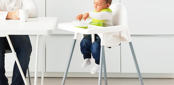 Baby in a white high chair.