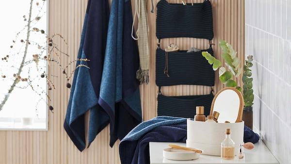 Kylpyhuone, jossa on pehmeitä tummansinisiä tekstiilejä ja luonnon valoa.