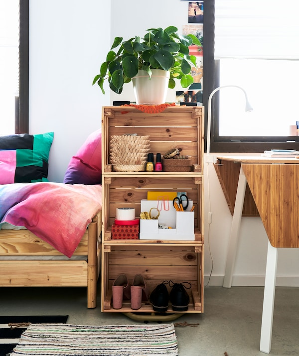 A lightly filled bookcase made of three wooden crates lain on the side and stacked. placed between a bed and small dining table.