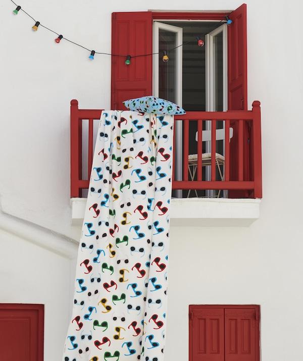 Višebojna tkanina s printom sunčanih naočala obješena je s crvenog balkona na bijelom zidu s višebojnim rasvjetnim lancem.