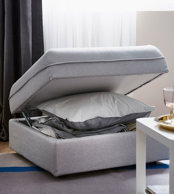 A light grey IKEA VALLENTUNA modular sofa unit, with lid opened to reveal a storage compartment for pillows and bedding.