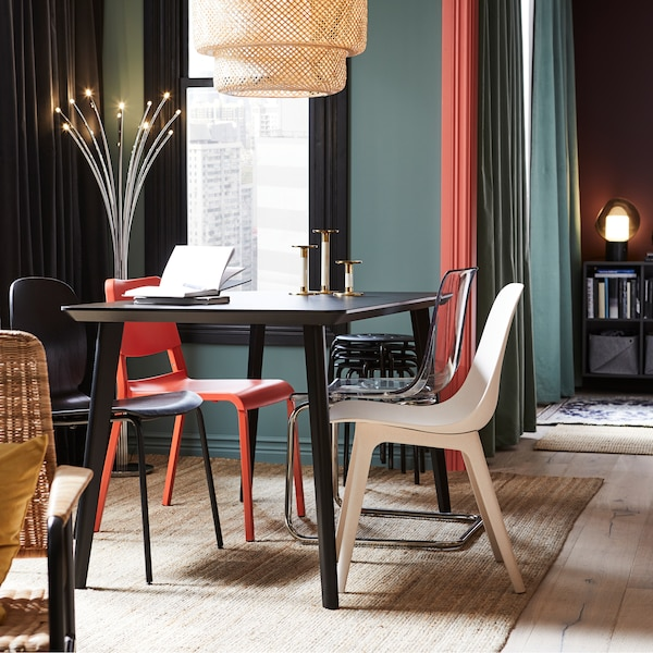 A kitchen with a dining area with a black table, red, white, and black chairs, a pendant lamp in bamboo and a rug in jute.