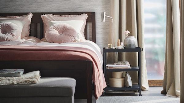 sypialnia, łóżko z różową pościelą, stolik nocny oraz beżowe zasłony w oknach