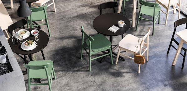 Black high table with 2 black chairs in a tile floor, blue wall café with black pendant light shining above.