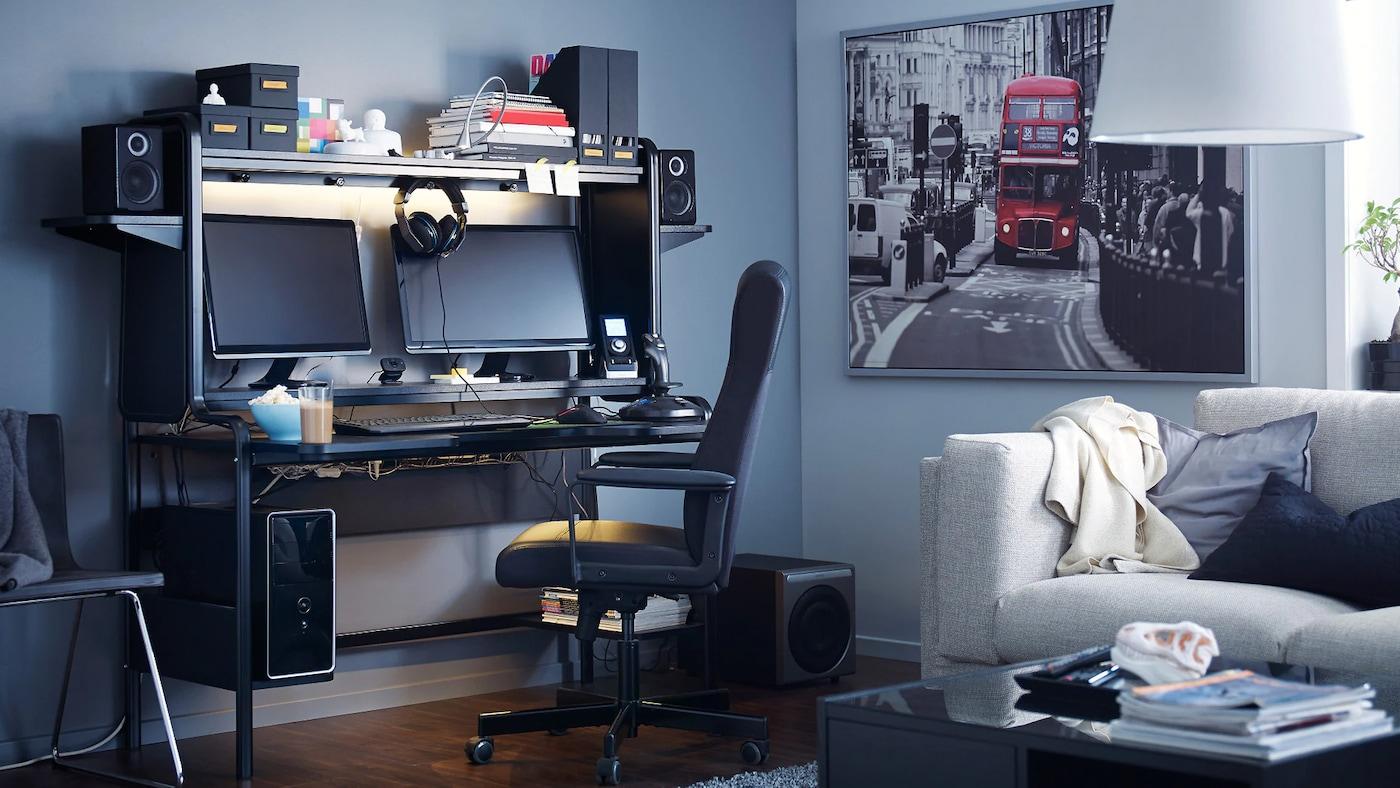 블랙 워크스테이션과 모니터 2대, 스피커, 수납공간이 있는 거실