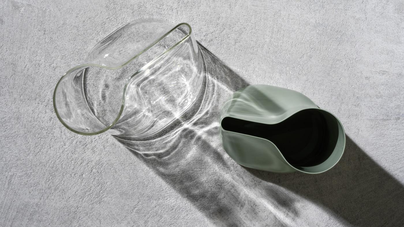 2 CHILIFRUKT vaser/vandkander af klart glas og grønt stål på en grå betonoverflade.