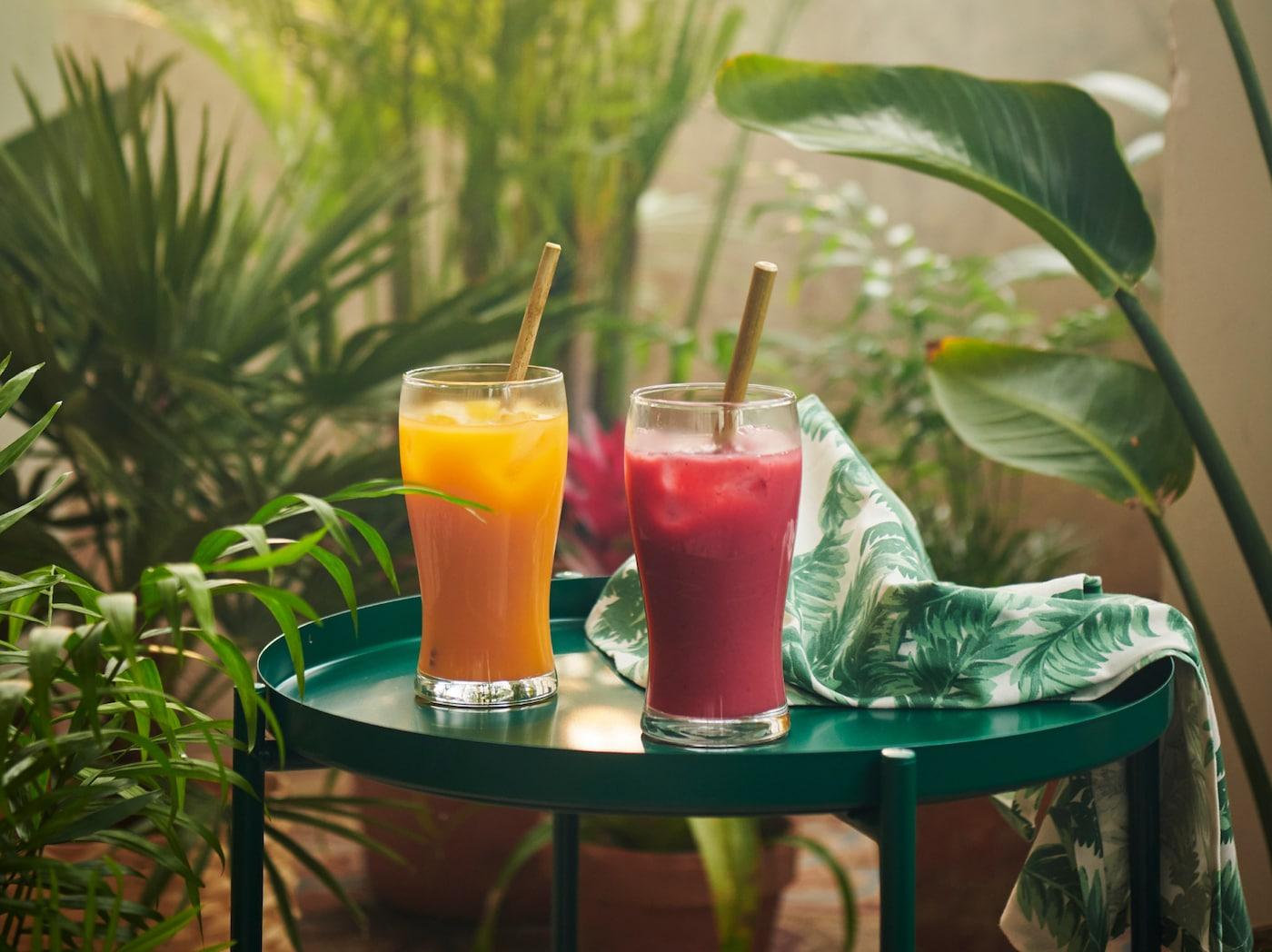 2 glas med FRUKTSTUND blendede smoothieblandinger – et med den gule blanding af tropiske frugter og et med den røde jordbærblanding – på et grønt bord mellem planter.