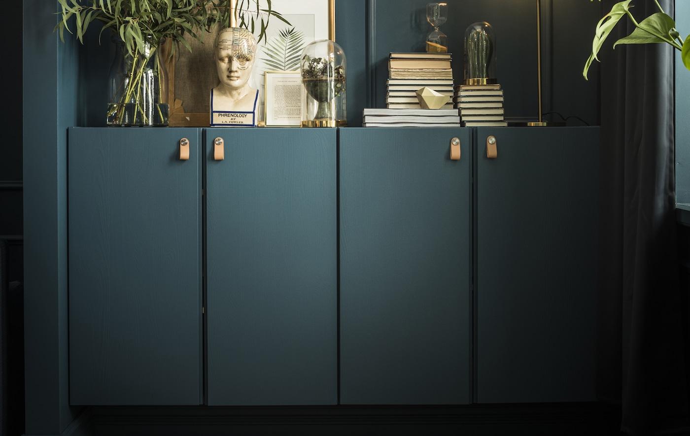 2 IVAR Schränke, in einem dunklen Grau-Grün genauso wie die Wand, darauf Bücher, Kunstwerke, Pflanzen