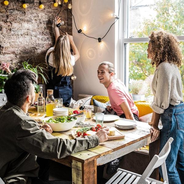 2 män sitter vid ett matbord och en kvinna som står tittar på när en annan kvinna hänger upp en ljusslinga.