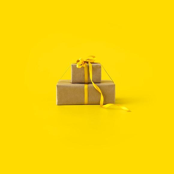 2 paquets cadeaux en papier kraft superposés devant un fond jaune
